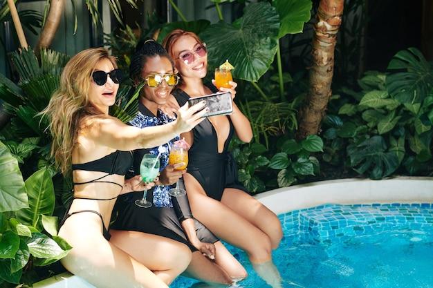 Groep mooie aantrekkelijke jonge vrouwen die selfie nemen wanneer ze op de rand van het zwembad zitten met glazen fruitcocktails in handen