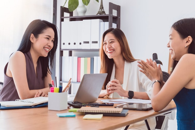 Groep mooie aziatische vrouwen die in bureau aan besprekingszaken samenkomen.