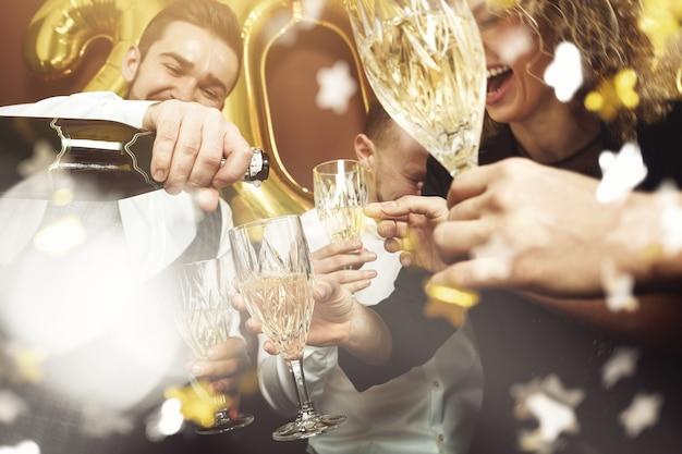 Groep mooie goed geklede feestgangers die nieuwjaar vieren en mousserende wijn drinken