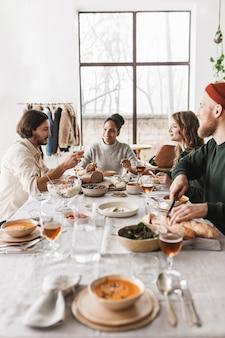 Groep mooie internationale vrienden zitten aan de tafel vol met eten met elkaar praten