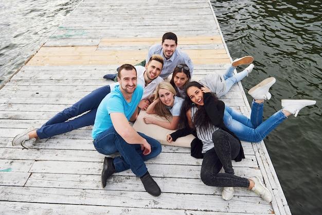 Groep mooie jonge mensen op de pier, de tevredenheid van vrienden creëert een emotioneel leven.