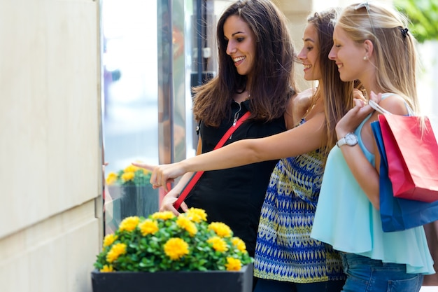 Groep mooie meiden kijken naar het winkelvenster.