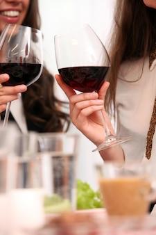 Groep mooie meisjes die van rode wijn genieten