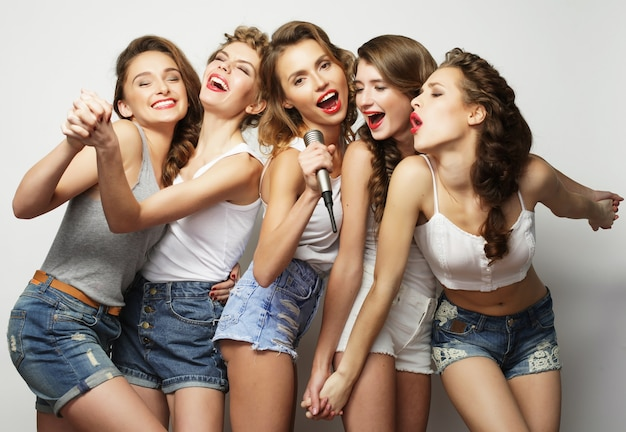 Groep mooie stijlvolle hipster meisjes karaoke zingen