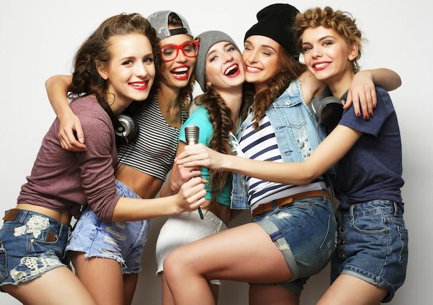Groep mooie stijlvolle hipstermeisjes die karaoke zingen