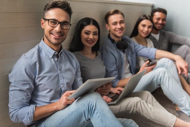 Groep mooie studenten in vrijetijdskleding die gadgets gebruiken