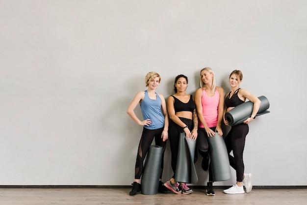 Groep mooie vrouwen die bij de gymnastiek stellen