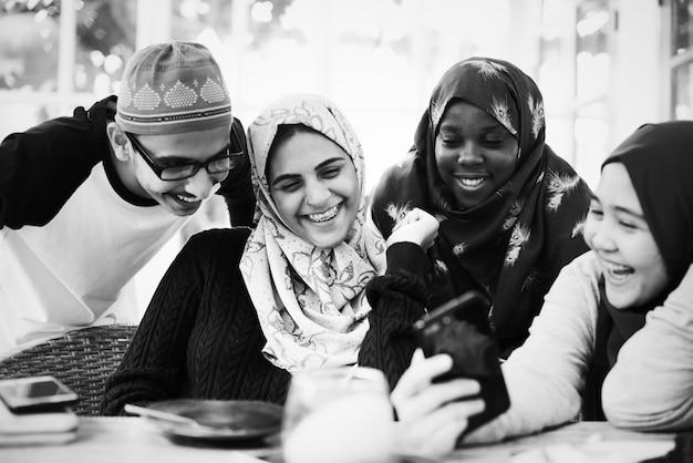 Groep moslimstudenten die mobiele telefoons gebruiken