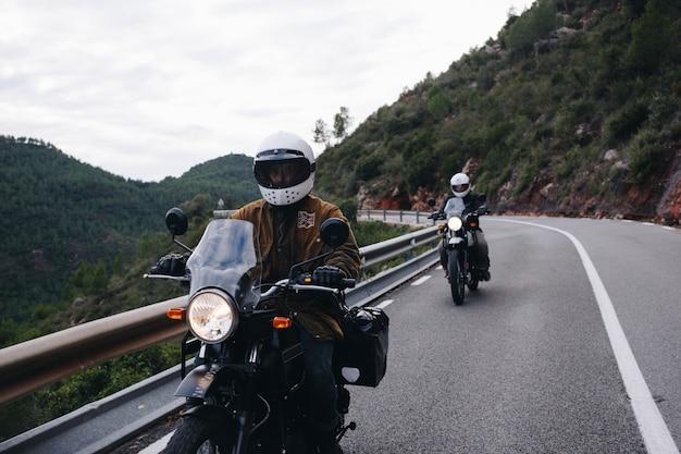 Groep motorrijders op bergweg