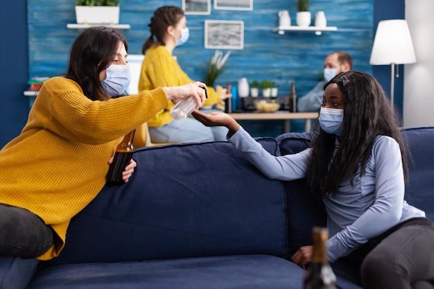 Groep multi-etnisch die handdesinfecterend middel gebruikt om verspreiding van het coronavirus te voorkomen terwijl ze samen tijd doorbrengen in de woonkamer thuis zittend op de bank met gezichtsmasker. conceptueel beeld.