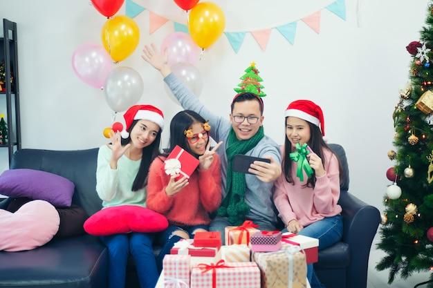 Groep multi-etnische medewerkers die selfie in kerstmanhoeden nemen bij bureaupartij,