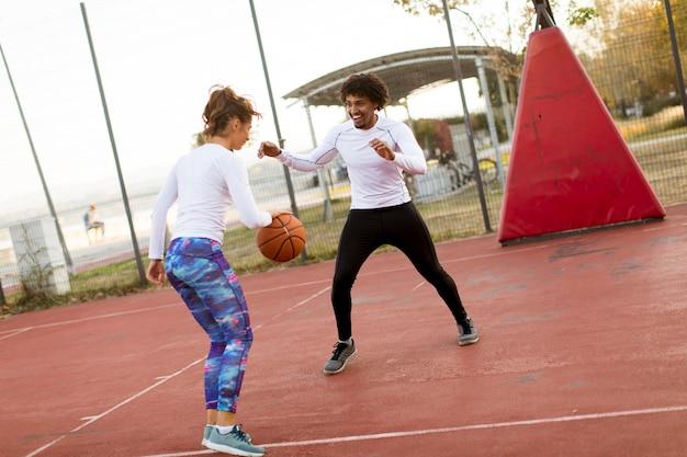 Groep multi-etnische mensen die basketbal op hof spelen