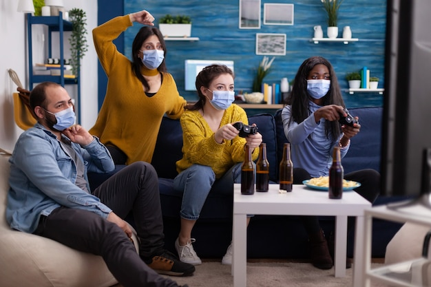 Groep multi-etnische vrienden die plezier hebben met het spelen van videogames in de huiskamer met joystick die gezichtsmasker draagt om covid19 niet te verspreiden en sociale afstand te bewaren. bierflessen, conceptueel beeld.