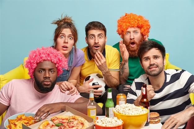 Groep multi-etnische vrienden staren, hebben ingehouden tijdens het kijken naar een zeer opwindend voetbalspel, zitten op de bank bij de tafel met pizza, bier en popcorn geïsoleerd op een blauwe muur. gekke emotionele reactie