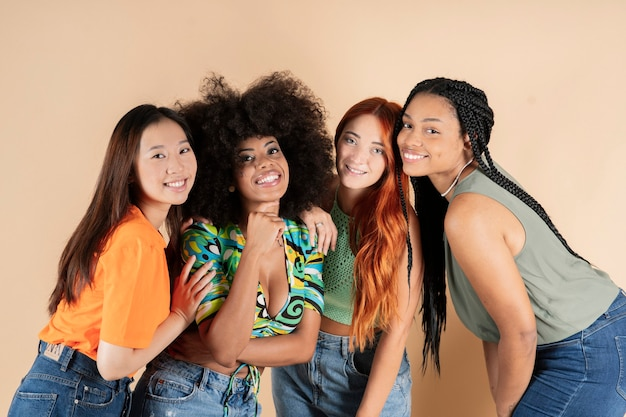 Groep multi-etnische vriendinnen, omarmen poseren in studio, gelukkig lachend