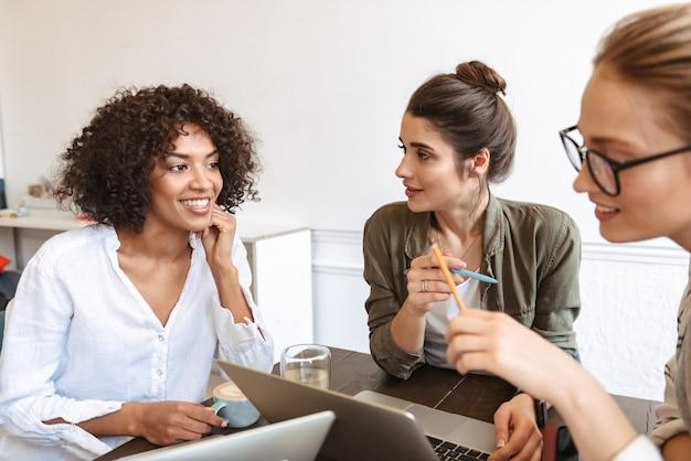 Groep multi-etnische vrolijke jonge vrouwen die samen studeren in de coffeeshop