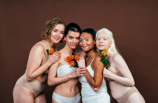 Groep multi-etnische vrouwen met verschillende soorten huid die samen in de studio poseren. concept over lichaamspositiviteit en zelfacceptatie Premium Foto