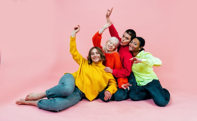 Groep multi-etnische vrouwen met verschillende soorten huid die samen in de studio poseren posing
