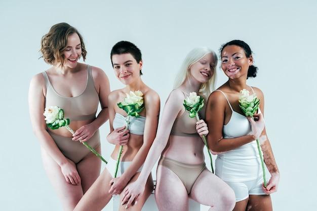 Groep multi-etnische vrouwen met verschillende soorten huid die samen in studio poseren concept over lichaam