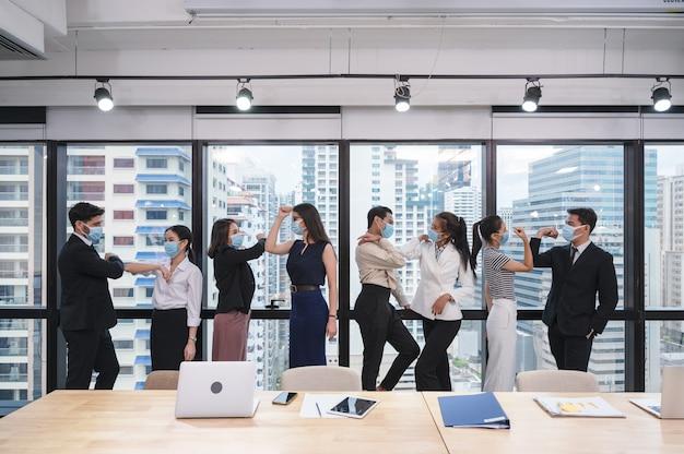 Groep multi-etnische zakenmedewerker die de groet van het gezichtsmasker met elleboogbult in nieuw normaal bureau dragen