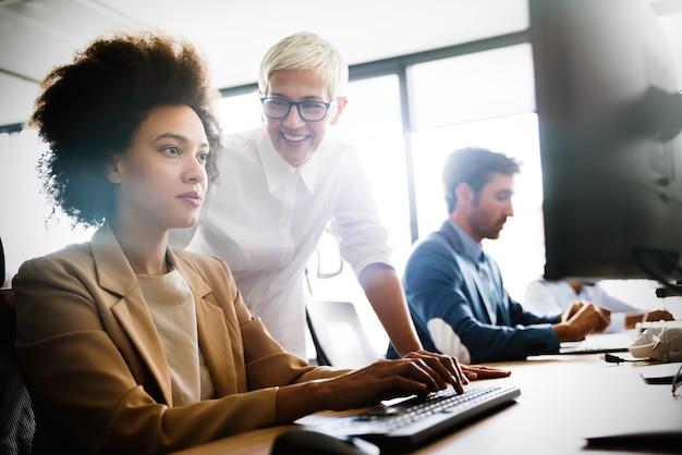 Groep multi-etnische zakenmensen die werken op een druk modern kantoor