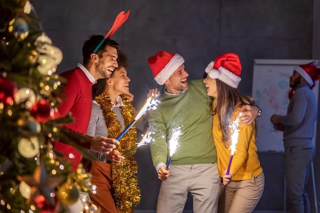 Groep multiculturele collega's die kerstavond vieren in hun bedrijf.