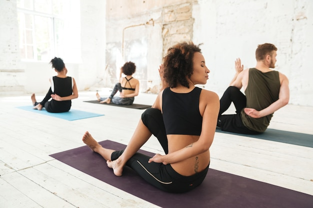 Groep multiculturele jongeren die yoga uitoefenen
