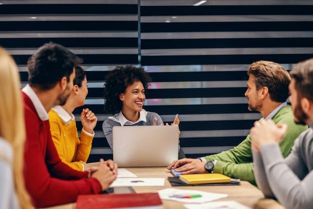 Groep multiculturele zakenmensen met bijeenkomst in directiekamer. gemengd ras vrouw praten over idee dat ze heeft.