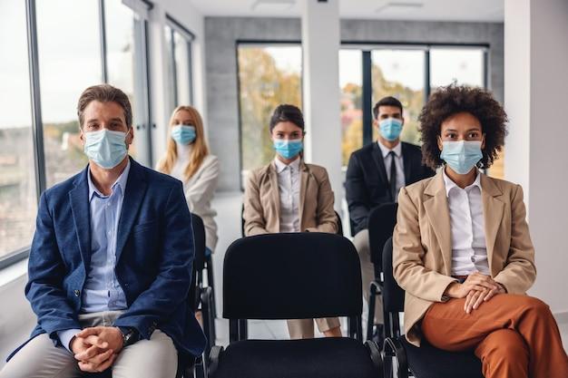 Groep multiculturele zakenmensen met gezichtsmaskers zitten en luisteren presentatie in corporate firma tijdens coronavirus.