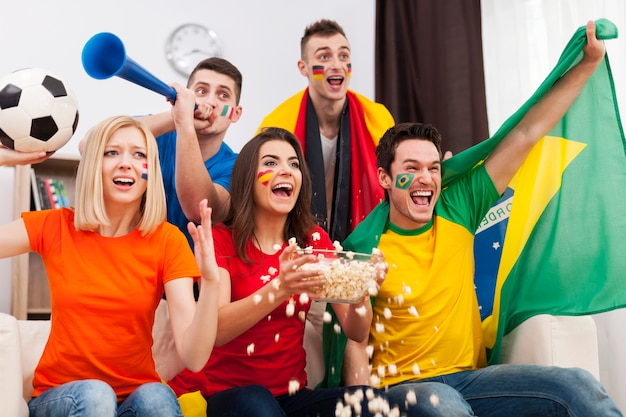 Groep multinationale mensen juichen voetbalwedstrijd thuis