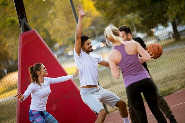 Groep multiraciale jongeren die basketbal in openlucht spelen