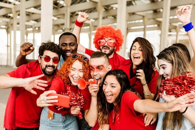 Groep multiraciale supporterssportfans die selfie met mobiele telefoon nemen
