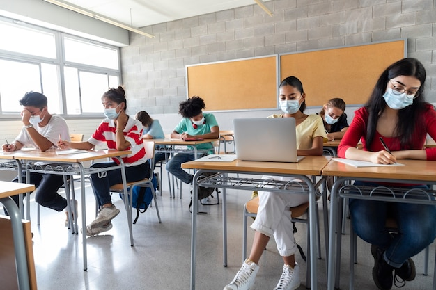 Groep multiraciale tiener middelbare scholieren die gezichtsmasker dragen in de klas. onderwijsconcept.