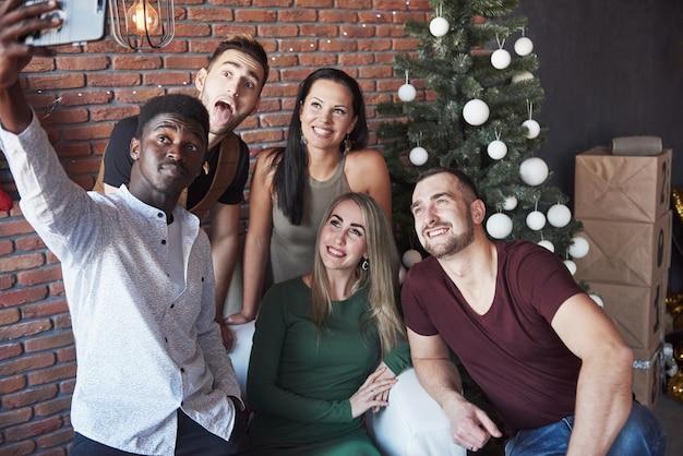 Groep ñ heerful oude vrienden communiceren met elkaar en maken een selfie foto. nieuwjaar komt eraan. vier het nieuwe jaar in een gezellige thuissfeer