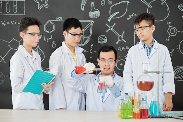 Groep nieuwsgierige vietnamese studenten in laboratoriumjassen en beschermende brillen die hun leraar bekijken die reagentia in bekerglas mengen