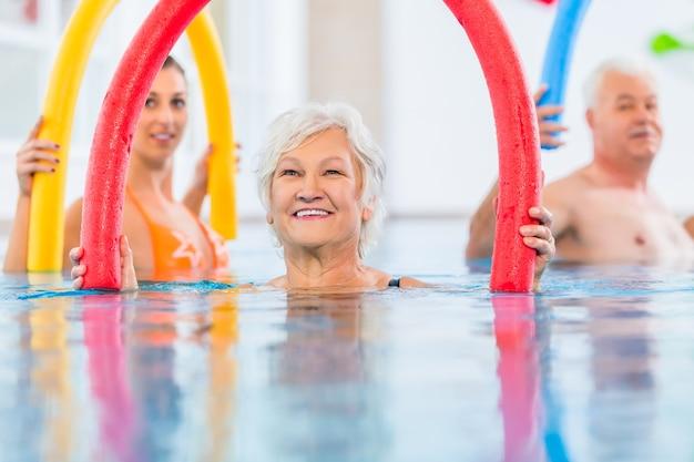 Groep of jonge en senior mensen in aquarobic fitness zwembad trainen met pool noodle