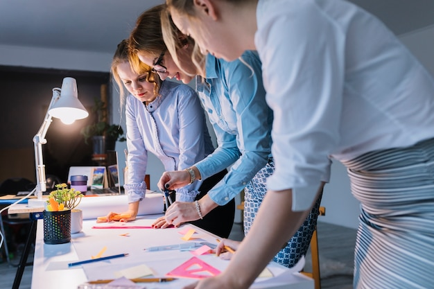 Groep onderneemsters die plan op witboek met instrumenten over bureau trekken op het werk