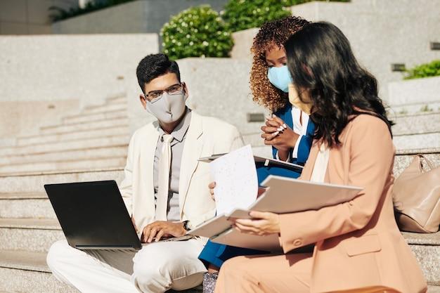 Groep ondernemers in medische maskers met bijeenkomst buitenshuis, bespreking van rapporten en planning van werkzaamheden aan project
