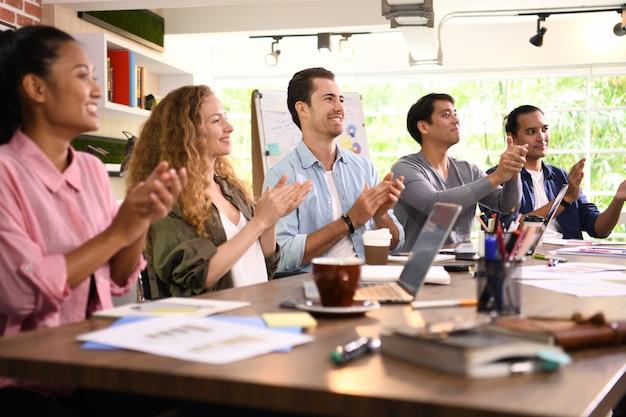 Groep ondernemers juichen en klappen voor een collega op kantoor