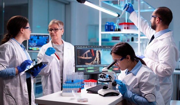 Groep onderzoeker in het virus van het laboratoriumonderzoek in de gezondheidszorg om vaccin te ontdekken onderzoekschemici die in het laboratorium werken met hightech die bloed- en genetische materiaalmonsters analyseert,