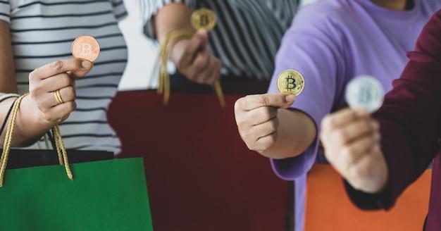 Groep onherkenbare vrouwen die cryptogeldmunten en een verscheidenheid aan kleuren boodschappentassen bij de hand houden. concept van cryptocurrency-betaling en digitaal geld dat in het echte leven van moderne mensen wordt gebruikt.