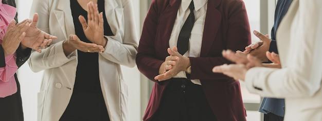 Groep onherkenbare zakenvrouwen die samen brainstormen aan het bureau. ze geven elk idee en elke beslissing in een memo op het bureau met zelfvertrouwen en klappen dan vrolijk in de handen.