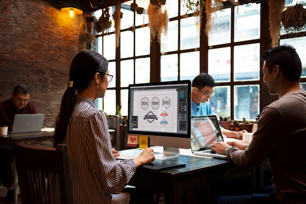 Groep ontwerpers die samenwerken in een café