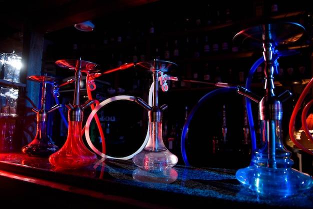 Groep oostelijke waterpijpen op lijst van een bar.