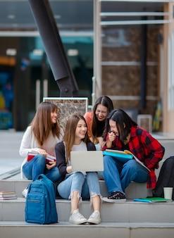 Groep opgetogen aziatische vrouwelijke studenten die zich verzamelen op trappen op de universiteitscampus en samen huiswerk maken terwijl ze een laptop gebruiken. concept voor goede vriend van het tienerleven.