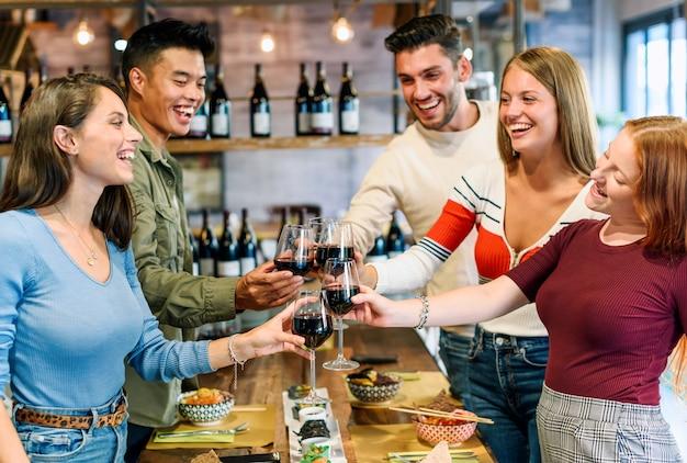 Groep opgewonden gelukkige jonge vrienden die samen een toast delen terwijl ze met hun glazen rode wijn klinken terwijl ze genieten van een maaltijd in een pub of restaurant om een speciale gelegenheid te vieren