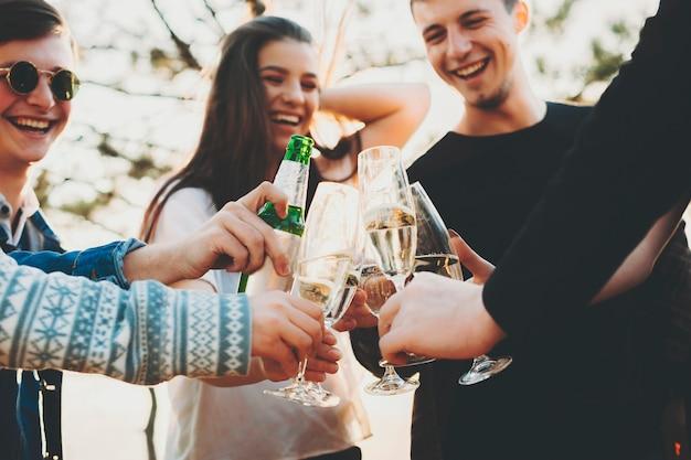 Groep opgewonden jonge mensen lachen en rammelende glazen alcohol met oogstvrienden terwijl ze tijd doorbrengen in de natuur op een zonnige dag. vrienden rammelende glazen en vieren in de natuur