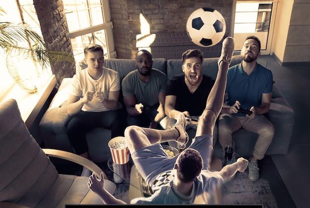 Groep opgewonden vrienden die thuis videogames spelen mannelijke gamers of fans