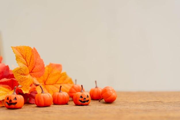 Groep oranje griezelige pompoenen en esdoornbladeren lag op een bruine retro houten tafelbladachtergrond