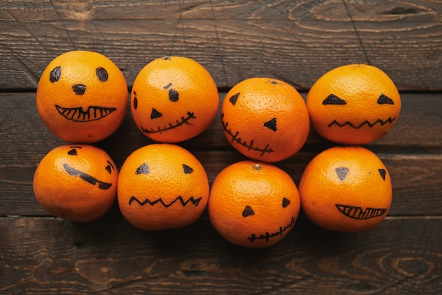 Groep oranje mandarijnen met jack o 'lantern gezichten getekend op hen liggend op donkerbruine houten tafel, plat leggen